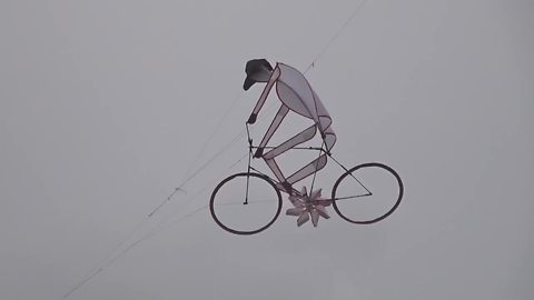 Guy riding bike is the coolest kite ever!