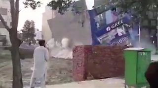 Dramatic footage shows three story building collapsing in Pakistan