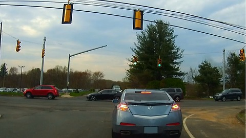 Car muscles his way through blocked intersection