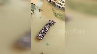 Lorry carries students across flooded campus to station - Video