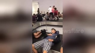 Exhausted passengers lay on conveyor belts amid 'biggest ever' Ryanair strike - Video