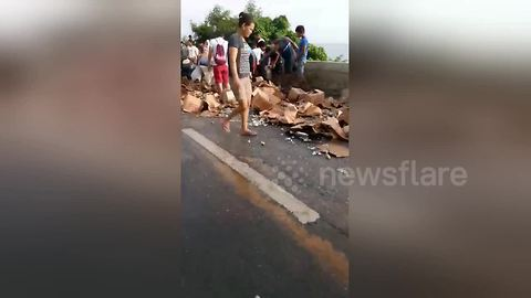 Frantic locals grab hundreds of bottles of brandy after lorry spilled its load