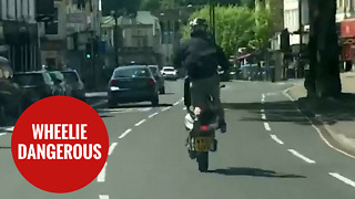 Moped rider wheelies down the wrong side of busy main road - Video