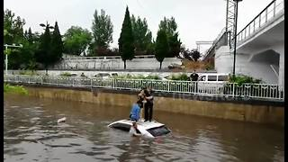 Woman rescued from car trapped in flooded street