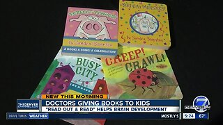 Doctors giving books to kids