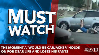 The moment a 'would-be carjacker' holds on for dear life and loses his pants - Video