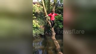 UK man falls in water trying to cross river on a log - Video