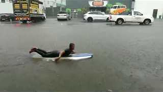 Surfer Takes to Flooded Streets as Storm Hits Durban - Video