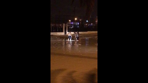 Men Wade Through Floodwaters in Kuwait City