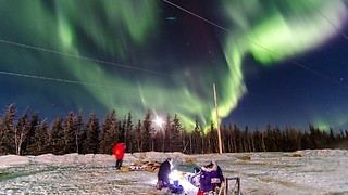 Sled Dog Team Rests Under Explosion of Northern Lights