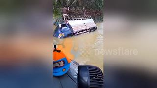 Trucks struggle through road after typhoon causes flooding in Vietnam - Video