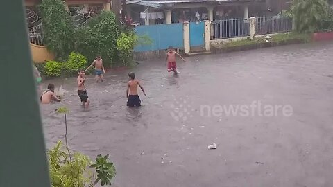 Filipino children make the most of the bad weather by playing in flooded street