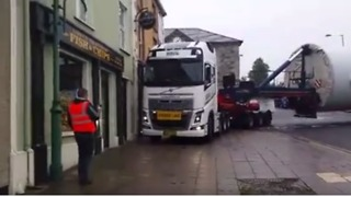 Truck Driver Towing Massive Wind Turbine Expertly Navigates Tiny Irish Town - Video