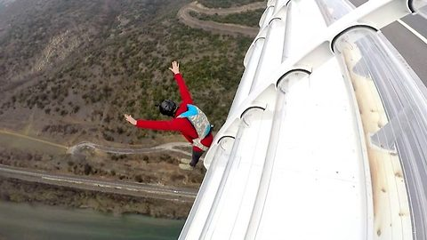 Adrenaline junkie base jumps after sliding from bridge