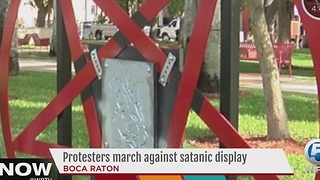 Protesters march against satanic display