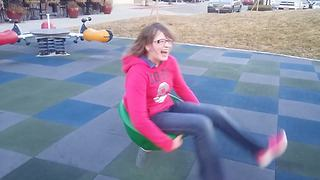 Young Girl Gets Dizzy After Spinning On A Kids' Playground