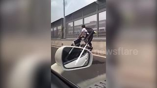 Motorcyclist pulls insane wheelies on busy highway - Video