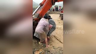 Rescuers use excavator to help villagers over flooded river - Video