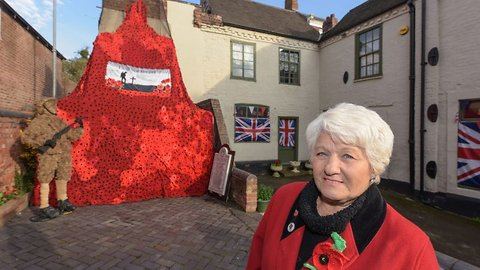 Thousands of knitted poppies hung from historic pub in stunt two years in the making