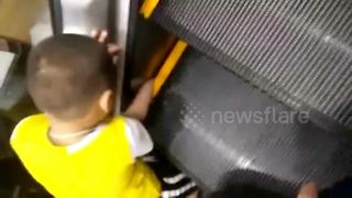 Chinese boy gets hand stuck in escalator - Video