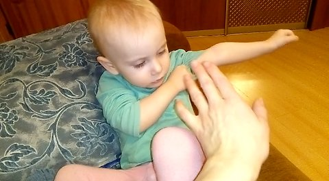 Cute baby like when her mother gently touches her hands.