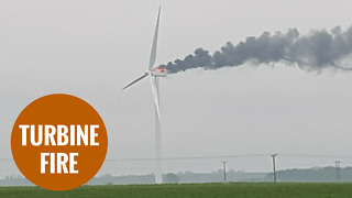 A wind turbine catches fire after thunder and lightening strikes - Video