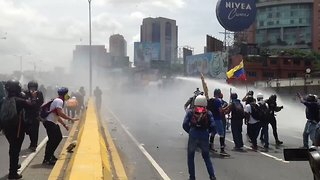 Caracas Protesters Face Off Against Water Cannons - Video