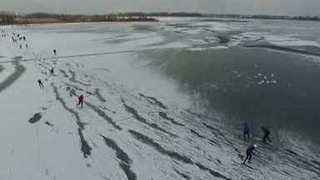 Ice Skaters Glide Across Frozen Dutch Lake