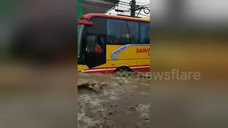 Buses struggle as Philippines storms turn road into raging river