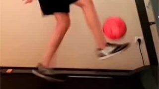 Young lad juggles soccer ball while walking treadmill