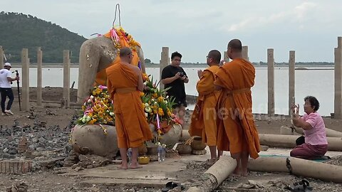 Thai locals flock to sunken Buddhist temple that has emerged from the water after severe drought