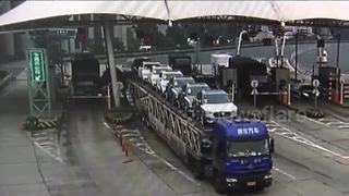 Overloaded truck knocks over toll booth with collector inside - Video
