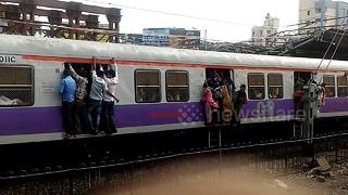 Commuters risk their lives clinging from open doors of packed train in Mumbai - Video