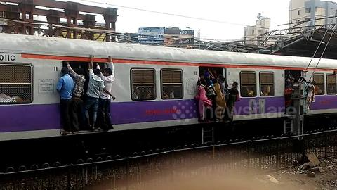 Commuters risk their lives clinging from open doors of packed train in Mumbai