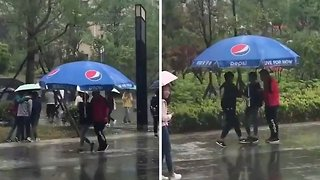 Two resourceful guys carry huge table parasol to cover themselves from heavy rain