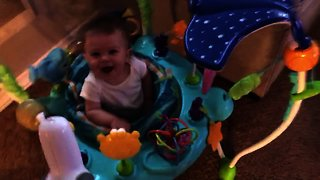 Baby can't stop laughing at dog playing tug-of-war