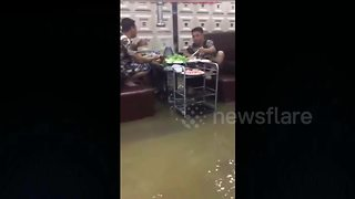 Restaurant customers continue meal despite flood
