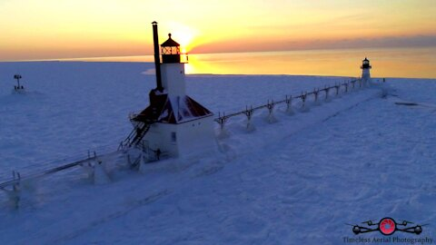 Stunning winter drone footage of lighthouse on frozen lake