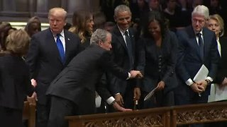 George W. Bush hands Michelle Obama a piece of candy at funeral for George H.W. Bush