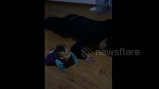 Baby knocks head on floor doing push-ups with dad - Video
