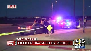 Officer dragged by suspect's vehicle, suspect still on the run - Video