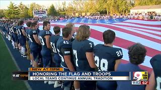 Rival high school teams hold giant U.S. flag together - Video