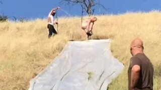 Naked guy meets a thorny end after slipping off giant slide