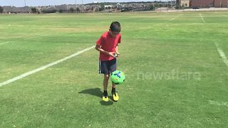 Boy solves Rubik's Cube while juggling soccer ball - Video