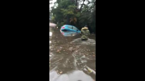 Elderly lady trapped in waist high flood water rescued by onlookers