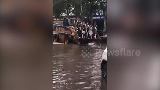 Digger driver charges two pounds a journey to transport commuters along flooded road - Video