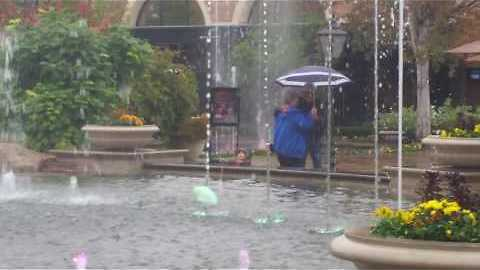 Elderly couple dances in the rain