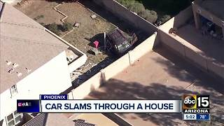 Car slams through Phoenix home - Video