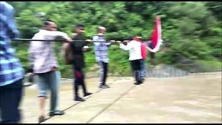Devotees and villagers balance on rope to cross flooded river - Video