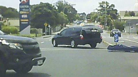 Shocking moment horrified motorist sees 'body bag' fly out of back of hearse at busy intersection